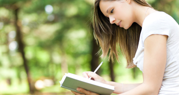 Woman writing on her diary at the park