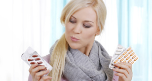 Frau überlegt bei Tabletteneinnahme