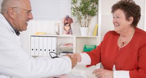 Hausarzt begrüßt seine senior Patientin mit Handschlag