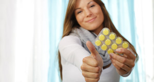 Junge Frau mit Tabletten hlt den Daumen hoch
